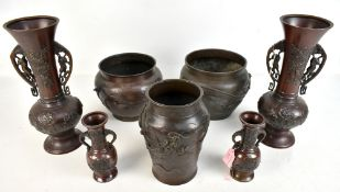 A pair of Japanese Meiji period bronze twin handled vases with foliate detail in relief, unmarked,