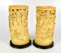A pair of 19th century Chinese Canton carved ivory tusk vases decorated with stylised figures in