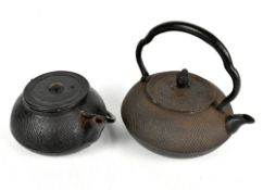 A Japanese cast iron teapot with fixed handle, the lid with pine cone finial, length 20cm, and a