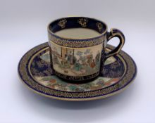 KINKOZAN; a Japanese Meiji period Satsuma cup and saucer decorated with panels of seated figures