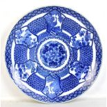 A large Japanese Meiji period blue and white charger decorated with peacocks and geese within floral