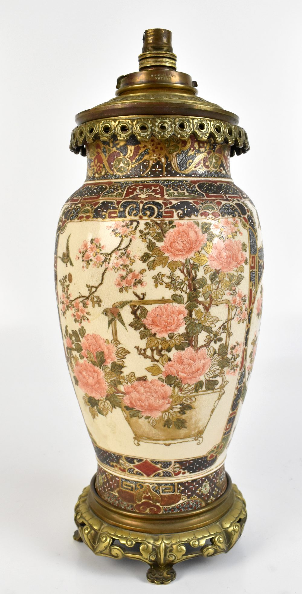 An early 20th century Japanese Satsuma oil lamp with brass mount, painted with birds and flowers,