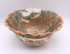 A large Japanese Meiji period Satsuma bowl with crimped rim and internal decoration of a palace with
