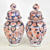 A pair of Japanese Meiji period Imari ribbed lidded vases with underglaze and gilt floral