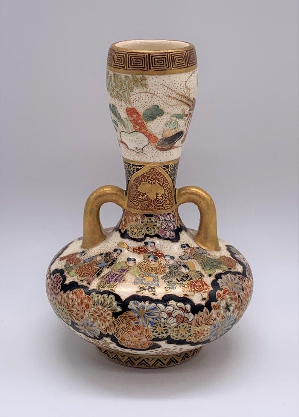 A Japanese Meiji period Satsuma twin handled vase of small proportions decorated with figures and