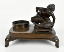 A Japanese Meiji period bronze inkstand featuring a figure holding a knife before a carp and inkwell