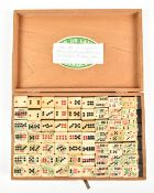 A box containing 128 Chinese bone faced and stained bamboo backed dominoes, each approx 2.3 x 2cm.