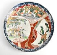 A Japanese Meiji period Imari wall charger painted with figures in landscape setting, diameter