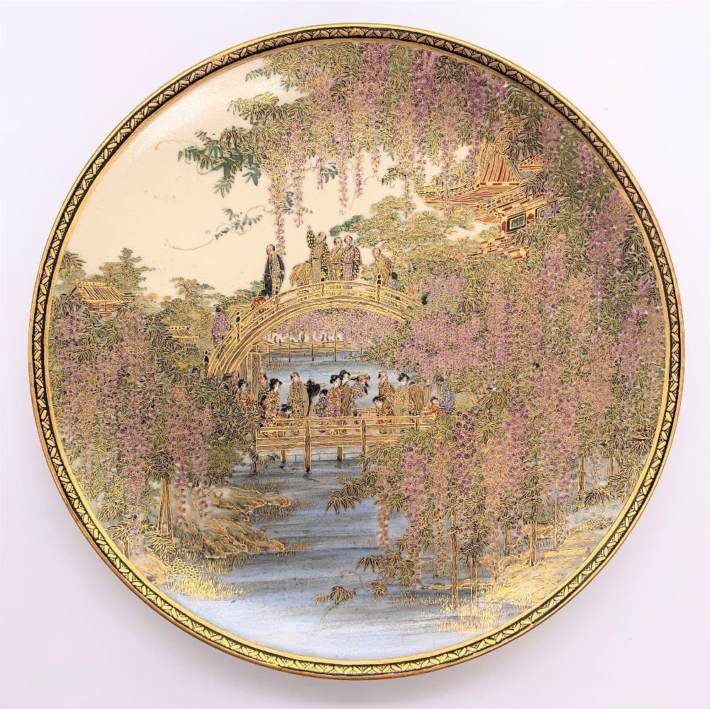 A fine Japanese Meiji period Satsuma plate decorated with figures on a bridge within cascades of