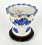 A Japanese porcelain pedestal bowl painted in underglaze blue with floral detail to interior and