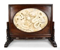 A large and impressive Chinese carved jade table screen, the central oval white jade panel depicting