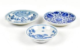 Three Chinese blue and white floral decorated saucer dishes, the larger two unmarked, the smallest