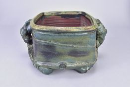 CHARLES BOUND (born 1939); an early stoneware twin handled vessel covered in metallic green glaze,