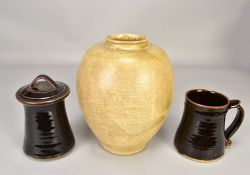 Leach Pottery; a stoneware jar and cover and a mug both covered in tenmoku breaking to kaki glaze,