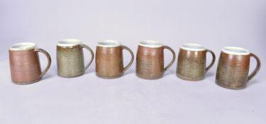 Leach Pottery; a set of six large stoneware mugs, tenmoku and ash glazes, impressed pottery marks,