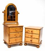 A pair of waxed pine bedside tables, each with three drawers, on bun feet and castors,