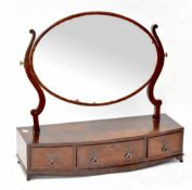 A 19th century mahogany toilet mirror with oval plate, on a pair of scroll supports,