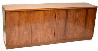 A mid-20th century rosewood sideboard comprising two pairs of cupboard doors,
