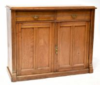 An Edwardian mahogany dresser base comprising two drawers and a pair of fielded and panelled
