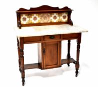 An Edwardian mahogany wash stand with marble top and tiled gallery above a base with cupboard and