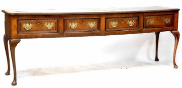 An 18th century oak dresser base of large proportions comprising four frieze drawers,
