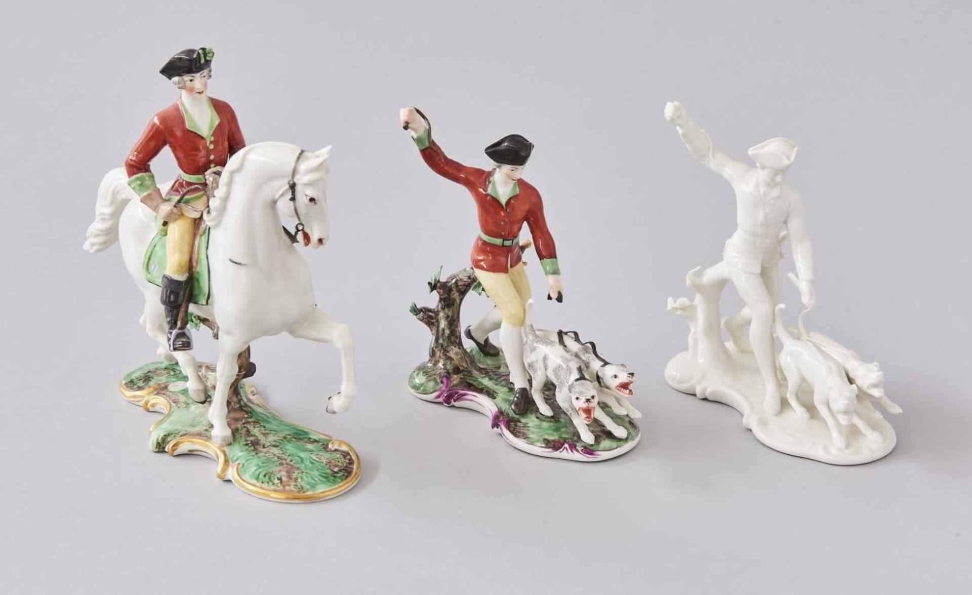 Los 15 - Konvolut 3 Nymphenburg FigurenJäger mit Hund bunt und weiß Höhe je 16,5 cm, Beschädigungen an