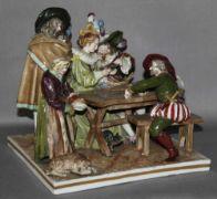 """Porzellan. Volkstedt. Polychrome bemalte Figurengruppeauf rechteckigem Sockel. Historisch gekleidete Männer und Frauen beim Kartenspiel an einem Tisch. Auf der Unterseite mit Porzellanmarke """"Krone"""" und Buchstabe """"N"""" in Unterglasurschwarzblau, Volkstedt (Ackermann & Fritze), aus der Produktion 1. Hälfte des 20. Jhrts. Höhe der Figurengruppe mit Sockel 19 cm. Sockel 20,4 x 20,4 cm. (41) * Zur Porzellanmarke vergl. Graesse (27. Auflage) 1991, S. 521. Schön gearbeitete histor..."""