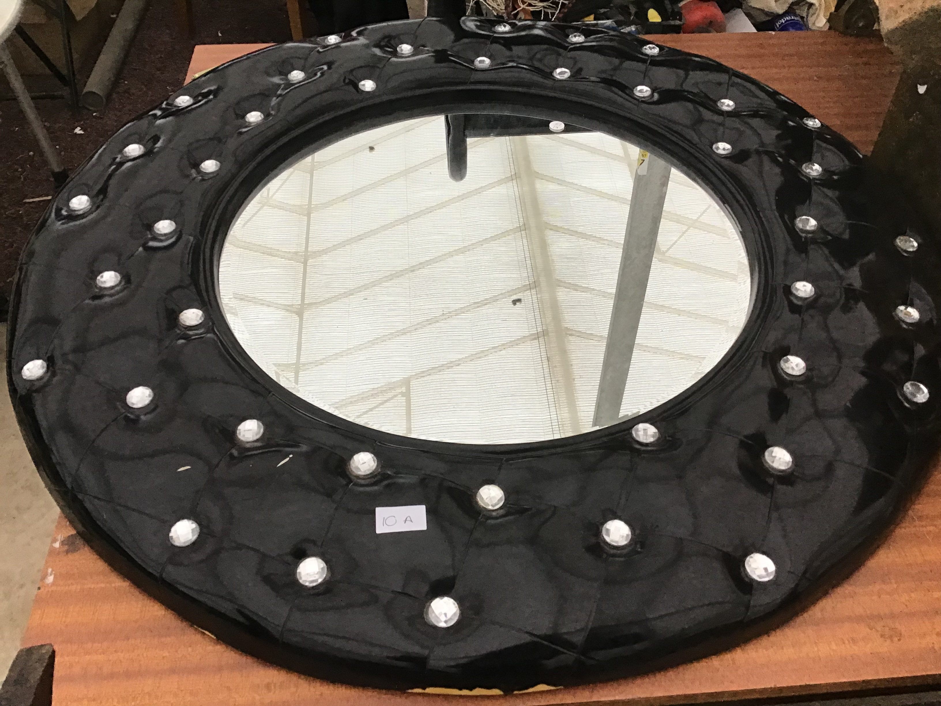 Lot 10A - A LARGE BLACK LEATHER EFFECT CIRCULAR MIRROR WITH CRYSTAL STUDS