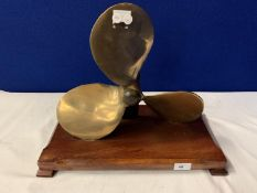 A VINTAGE BRASS PROPELLER MOUNTED ON A WOODEN BASE