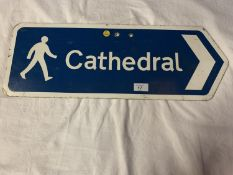 A BLUE AND WHITE METAL STREET SIGN POINTING THE WAY TO THE CATHEDRAL