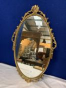 AN OVAL ORNAMENTAL GILT METAL FRAMED MIRROR