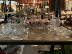 A LARGE QUANTITY OF GLASSWARE TO INCLUDE FOUR DECANTERS AND SIX SERVING PLATES ETC