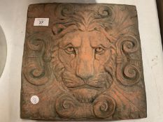 A SQUARE TERRACOTTA STONE TILE OF A LION'S HEAD IN RELIEF