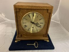 AN OAK CASED BRAVINGTONS LTD (RENOWN SUPER) EIGHT DAY MANTEL CLOCK WITH BRASS CLAW FEET AND KEY