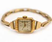 A ladies mechanical wristwatch stamped 18k 0.750, on a 9ct expandable bracelet, approx gross