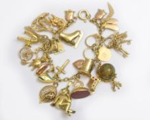 A 9ct charm bracelet, most charms H/M some stamped 9ct, approx gross weight 50gms