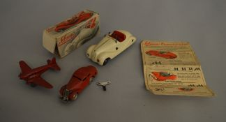 A boxed vintage Schuco Examico 4001 tinplate clockwork open Tourer in ivory with red seats,