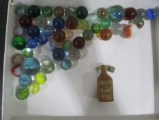 A small quantity of vintage marbles along with a wooden Cointreau bottle containing two miniature