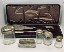 Five hallmarked silver topped bottles along with a cased set of fish servers
