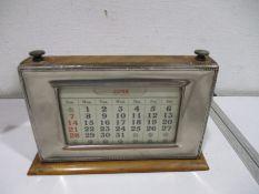 A silver plated perpetual desk calendar