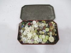 A collection of various buttons in a vintage tin etc