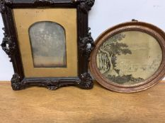 A needlework landscape depicting a river landscape with church and figures in oval frame along