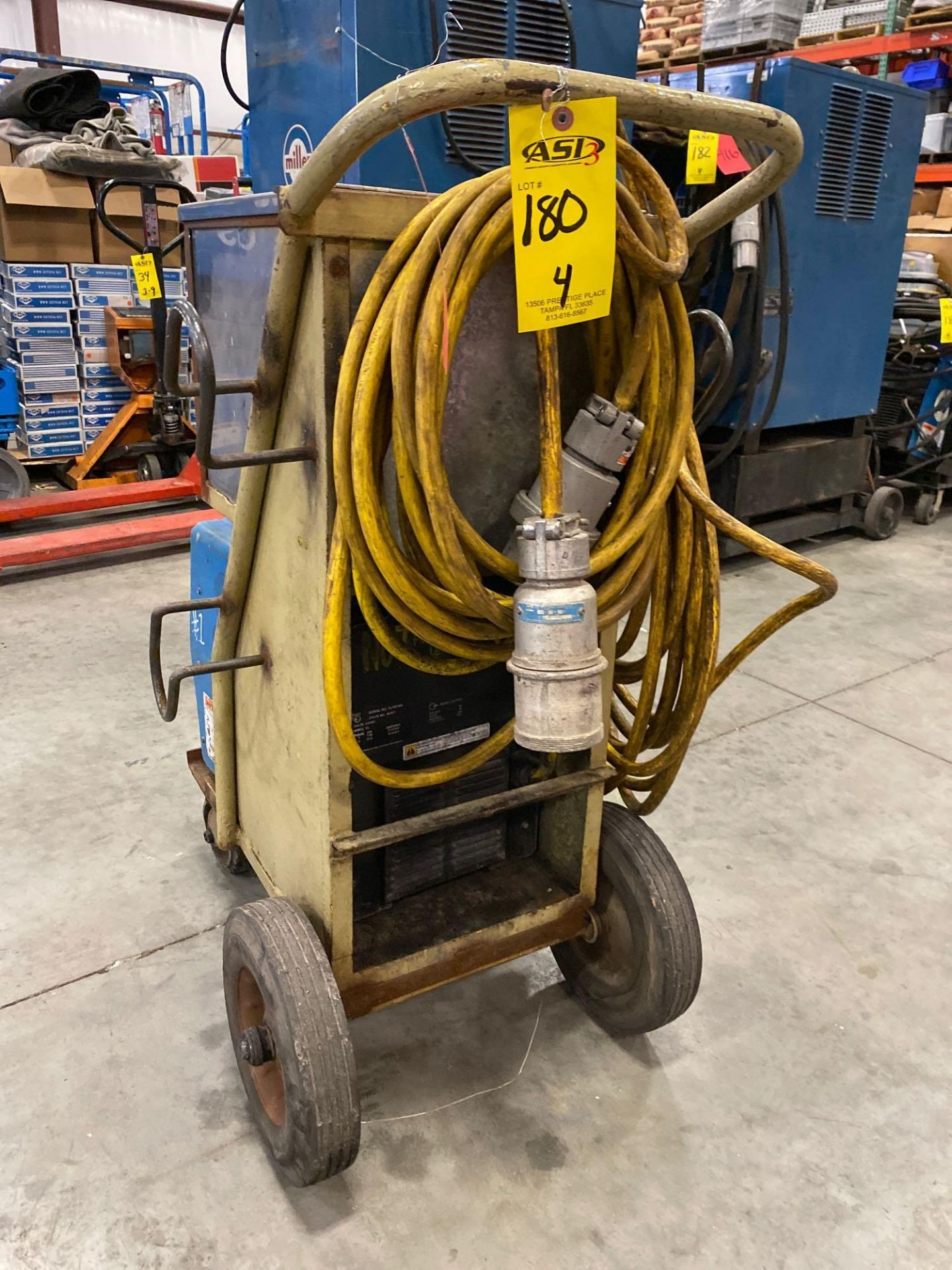 Lot 180 - MILLER XMT 304 WELDER WITH CART AND STORAGE BIN