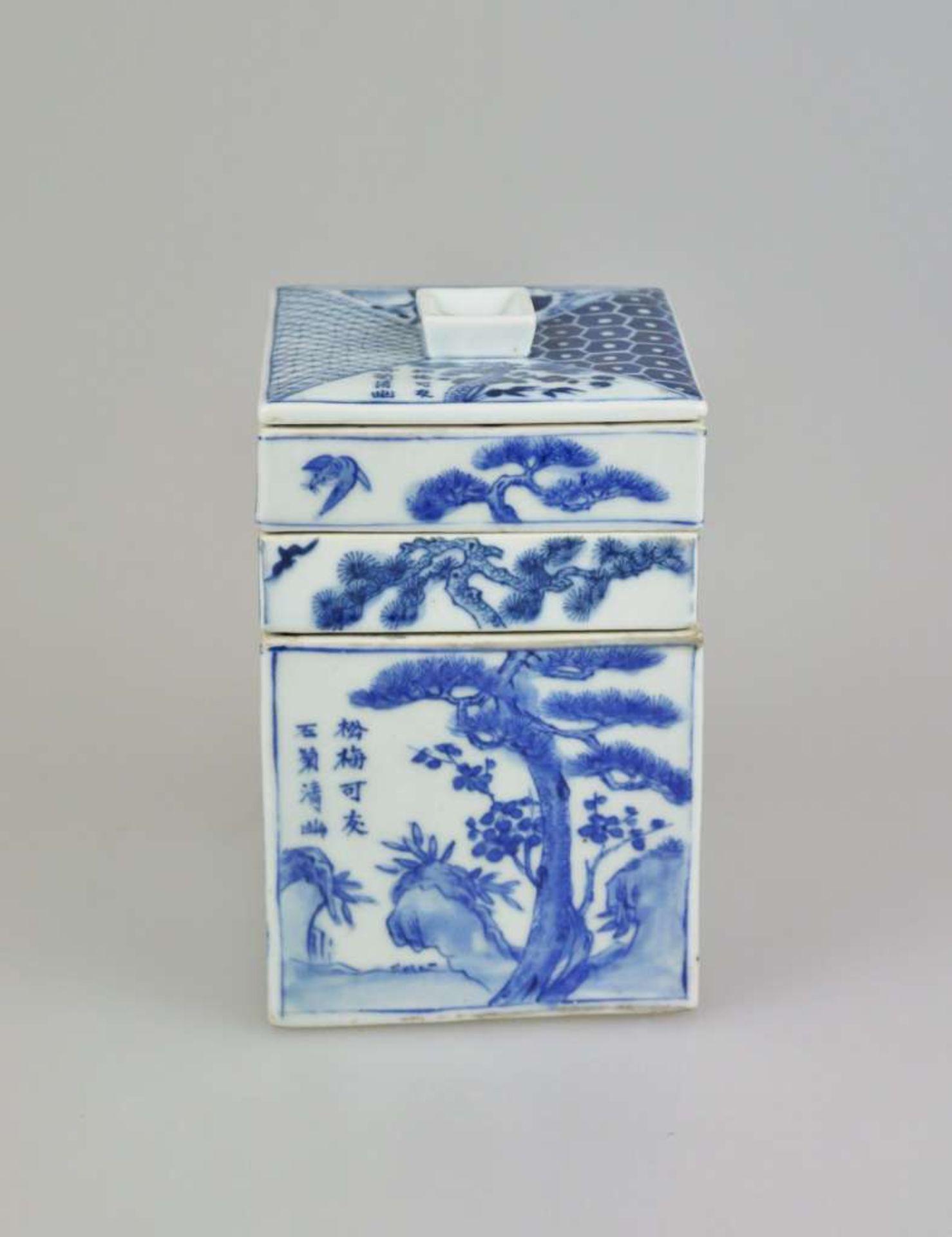 Ein blau-weiß quadratischer Schreibwarenbehälter mit Abdeckung, bestehend aus vier Teilen, ei