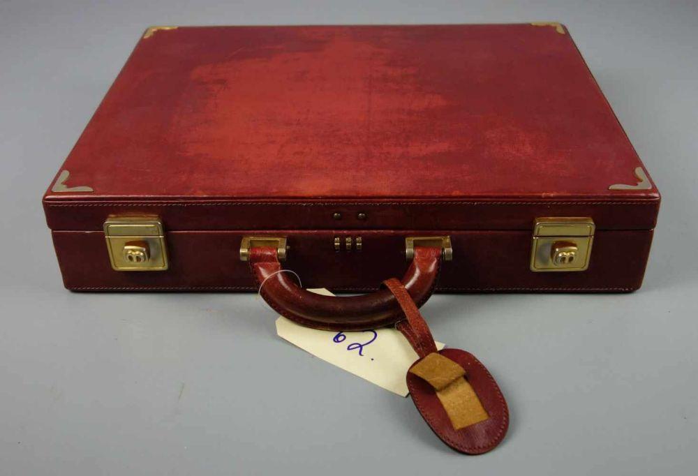 ROTER MÄDLER AKTENKOFFER / red leather briefcase, 2. H. 20. Jh., rotes Leder mit goldfarbenen Metallapplikationen. Eckige Form mit Griff und Scharnierdeckel sowie Zahlenschloss. Innenauskleidung mit
