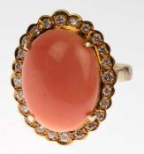 Ring, 585er GG, besetzt mit ovalem Korallen-Cabochon von ca. 9,50 ct., umrandet vo 24Brillanten