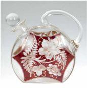 Karaffe, um 1900, beidseitig rot lasiert und floral geschliffen, am Ausguß bestoßen und