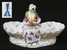 """Figurenschale """"Köchin"""". MEISSEN um 1860, Modellnummer C 81. Zwischen zwei Muschelschalen sitzende<"""