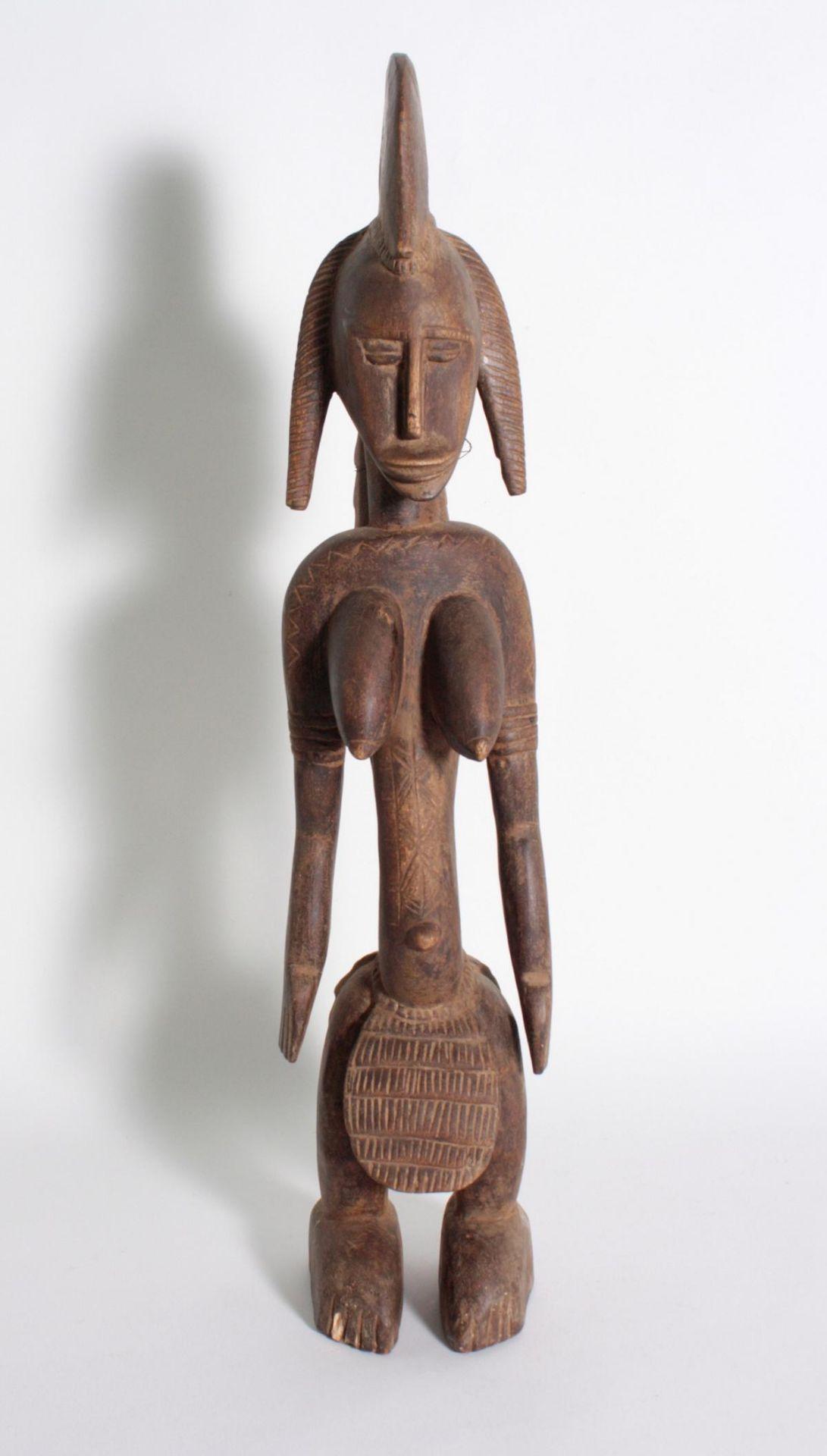 Stehende Frauenfigur, Senufo/Elfenbeinküste, 1. Hälfte 20. Jh.Bräunliches Holz. Stehende Frauenfigur