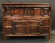 A 17th century oak duodarn, oversailing top with turned pendant finials, above panels and cupboard